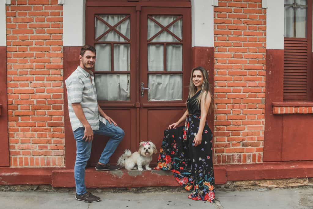 A man and a woman posing in front of a door with a dog