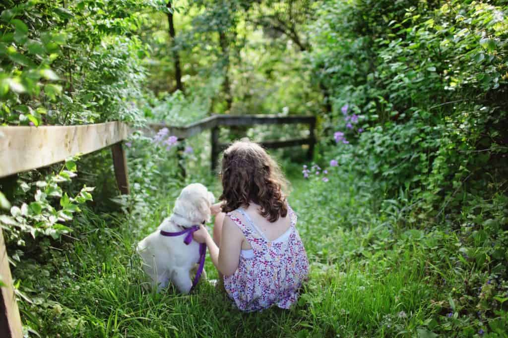 A girl and a puppy in the middle of the forest