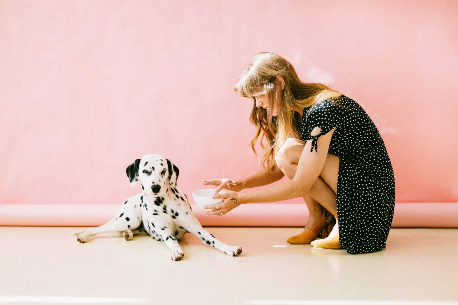 Woman holding a bowl while trying to feed her Dalmatian